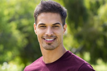 Photo for Portrait of young latin man with toothy smile looking at camera. Happy handsome guy in casual at park in a summer day. Closeup face of stylish man relaxing outdoor. - Royalty Free Image
