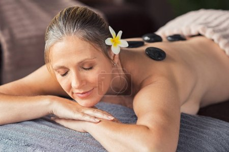 Beautiful senior woman with eyes closed receiving hot stone massage at salon spa. Portrait of mature woman relaxing during lastone therapy. Senior lady lying on spa table with black lava stones on back.