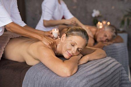 Photo pour Couple mature avec les yeux fermés recevant la bougie de massage épaule au spa. Couple de personnes âgées se trouvant sur la table de massage détente avec traitement de cire chaude de bougie. Concept de bien-être et de la fesse. - image libre de droit