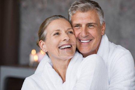 Photo pour Mari souriant embrassant une femme gaie par derrière au spa. Couple senior, bénéficiant d'une accolade romantique au centre de bien-être après massage en riant. Senior homme et femme en blanc peignoir relaxant au spa. - image libre de droit
