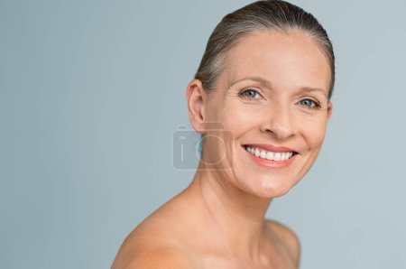 Photo for Portrait of a smiling senior woman looking at camera. Closeup face of mature woman after spa treatment isolated over grey background. Anti-aging concept. - Royalty Free Image