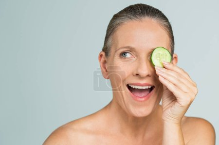 Photo pour Portrait de mature femme nue belle souriant yeux se cachant derrière une tranche de concombre. Portrait de beauté d'une femme senior souriante isolée sur fond gris. Drôle femme senior dans une ambiance ludique qui couvre les yeux avec une tranche de concombre. - image libre de droit