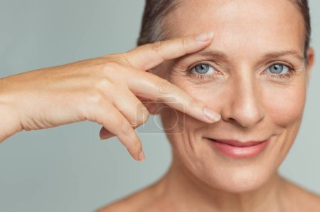 Portrait of smiling senior woman with perfect skin showing victory sign near eye on grey background.  Closeup face of mature woman showing successful results after anti-aging wrinkle treatment. Beauty mature skin care concept.