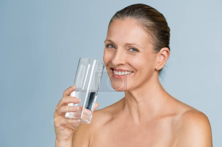Portrait of happy mature woman holding a glass of filtered water isolated on grey background. Cheerful senior woman holding half filled glass of water and looking at camera. Health care concept and hydration for perfect beauty skin.