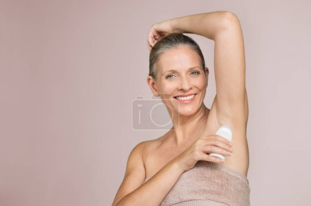Smiling woman applying deodorant in armpit isolated on grey background with copy space. Beautiful senior woman putting antiperspirant stick after shower and looking at camera.