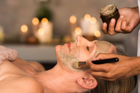 Senior woman relaxing while beautician getting purifying clay mask on her face. Closeup hand of masseuse applying mud from jar container on face of mature lady in spa center. Anti aging facial treatment with brush.