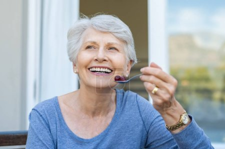 Cheerful senior woman holding red grapes in spoon and make a beautiful white smile. Smiling old woman looking away while eating fresh fruits for breakfast. Mature woman enjoying old age and healthy eating.