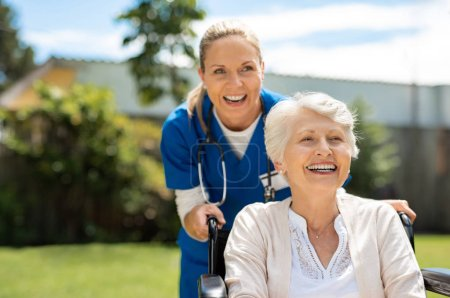 Happy nurse and elderly woman sitting in wheelchair enjoying outdoor treatment session. Beautiful nurse with laughing senior woman in wheelchair at outdoor park. Smiling disabled old lady in wheelchair at park.