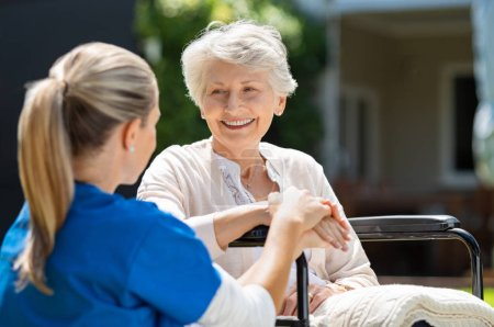 Smiling senior patient sitting on wheelchair with ...