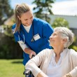 Nurse taking care of old woman in wheelchair outdo...
