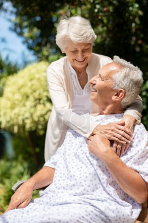 Photo for Senior woman hugging man in medical cloth in the hospital garden. Loving wife embracing old hospitalized husband sitting on bench at outdoor lawn. Caring wife supporting husband in illness in a private medical clinic. - Royalty Free Image