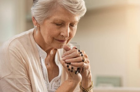 Photo pour Senior woman praying while holding christian symbol of crucifix. Old woman praying to god with hope and closed eyes. Elderly believer make a prayer with faith holding rosary in hands. - image libre de droit