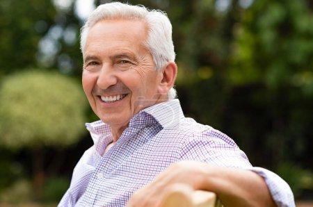 Senior homme assis sur un banc au parc et regardant la caméra. Portrait de vieillard sain de détente en plein air. Ancien grand-père âgé, profiter de la vie après la retraite