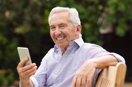 Photo for Senior man using smartphone while sitting on bench at park. Portrait of handsome old man using smart phone outdoor. Happy smiling grandfather holding mobile phone and looking at camera. - Royalty Free Image