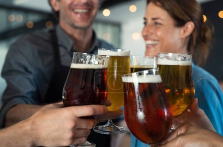 Photo for Happy friends clinking glasses of tap beer. Closeup hands of mature men and women toasting with draught beer. Hands holding beer for raising a toast to celebrate. People cheering to success with pints of beer. - Royalty Free Image