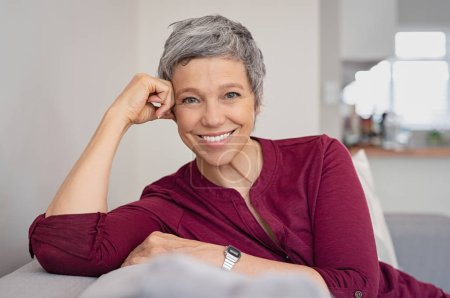 Photo for Portrait of smiling senior woman relaxing on couch at home. Happy mature woman sitting on sofa and looking at camera. Closeup of lady relaxing at home. - Royalty Free Image