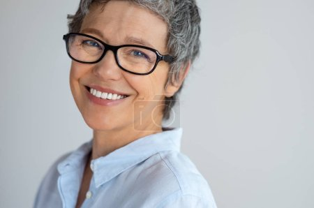 Photo pour Portrait d'une femme senior avec lunettes en regardant la caméra isolée sur fond gris. Femme d'affaire mature joyeuse portant des lunettes nouvelles tendances et souriant. Gros plan visage d'entrepreneur à succès en riant. - image libre de droit