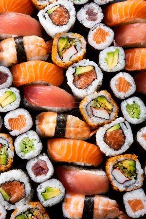 Photo pour Vue de dessus d'une variété de plats de sushi. Vue d'angle élevé des nigiri, maki, hosomaki, uramaki et rouleau avec thon, saumon, avocat et crevettes dans une rangée. Cuisine japonaise traditionnelle avec poisson cru et riz. - image libre de droit
