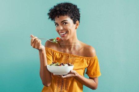 Photo pour Belle jeune femme africaine mangeant de la salade fraîche avec des tomates cerises. Portrait de femme souriante heureuse dans un régime isolé sur fond bleu. gai brésilien fille avec bouclé cheveux manger frais légumes tout en regardant caméra avec copie espace . - image libre de droit