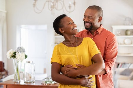 Photo for Mature married couple embracing in living room while looking at each other. Newly wed african couple in love hugging at home. Romantic husband with beautiful wife in love at home with copy space. - Royalty Free Image