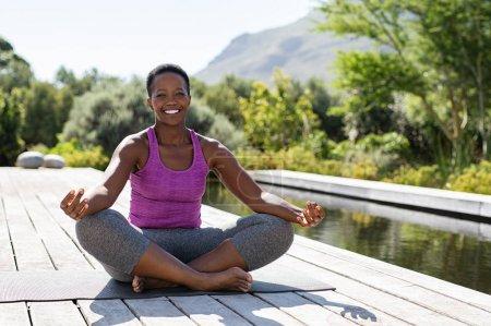Photo pour Portrait de femme souriante en position lotus près de la piscine regardant la caméra. Femme mûre noire en bonne santé méditant et assise dans une pose de lotus sur un tapis de yoga. Dame heureuse dans la pose zen faisant la méditation . - image libre de droit