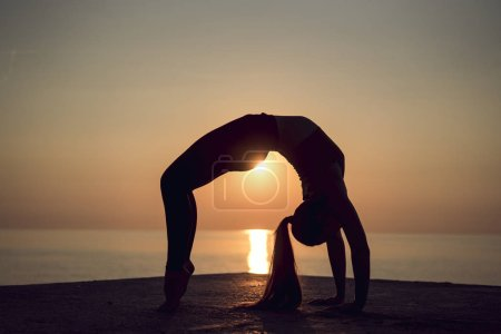 Photo for Silhouette of young gymnast doing a wheel pose on the beach at sunset. Woman practicing yoga or pilates on the pier. Bridge Pose, Urdhva Dhanurasana (Upward Bow), Chakrasana (Wheel). Side view. - Royalty Free Image