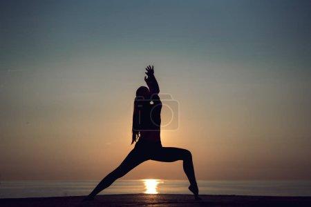 Photo pour Silhouette de jeune femme pratiquant le yoga seule sur la plage au coucher du soleil. Méditation féminine, forme physique et mode de vie sain. Fille de sport faisant des étirements et de l'exercice à l'extérieur pendant les vacances . - image libre de droit