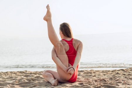 Photo for Young woman practicing yoga, stretching legs to be flexible and fit.. Healthy girl doing exercises on the beach on the sunrise. Relaxing early in the morning. Concept of calmless and health. - Royalty Free Image