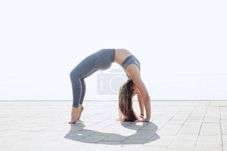 Photo for Young gymnast doing a wheel pose in urban exterior. Woman practicing yoga or pilates with white sky on the background. Bridge Pose, Urdhva Dhanurasana (Upward Bow), Chakrasana (Wheel). Side view. - Royalty Free Image