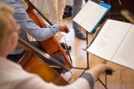 close up of a man and woman playing the cello, a real concert