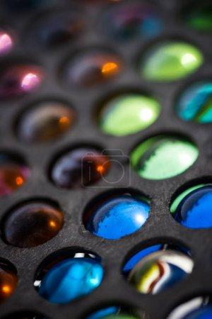 Photo pour Belle image abstraite de fond de billes de verre vintage coloré dans une vitrine en métal avec l'utilisation de la mise au point douce, brouillant l'arrière-plan & premier plan autour du point de mise au point principal - image libre de droit