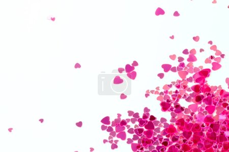 Pink sequins on a pink pastel background with confetti as asterisks.