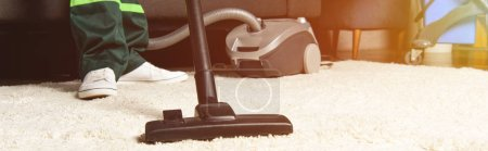 Photo for Cropped shot of professional worker using vacuum cleaner and cleaning white carpet - Royalty Free Image