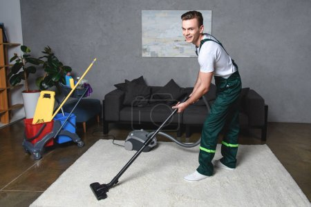 handsome young man cleaning white carpet with vacuum cleaner and smiling at camera