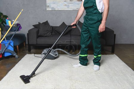 cropped shot of man using vacuum cleaner and cleaning white carpet
