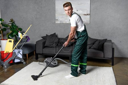 young professional cleaning company worker using vacuum cleaner