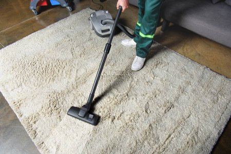 Photo for High angle view of man using vacuum cleaner and cleaning white carpet - Royalty Free Image