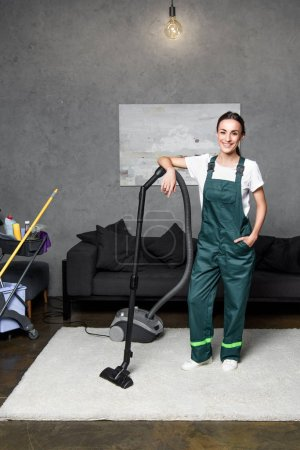 Photo for Happy young female cleaning company worker leaning at vacuum cleaner and smiling at camera - Royalty Free Image
