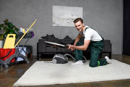 Photo for Handsome young man using vacuum cleaner and smiling at camera, professional carpet cleaning - Royalty Free Image