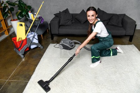 high angle view of happy young female cleaner using vacuum cleaner and smiling at camera while cleaning white carpet