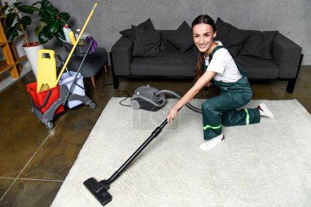Foto de Alto ángulo de visión de la mujer joven feliz con aspirador limpiador y sonriendo a cámara mientras limpieza alfombra blanca - Imagen libre de derechos