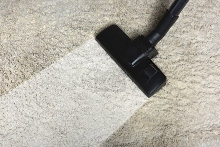 Photo for Close-up view of cleaning white carpet with professional vacuum cleaner - Royalty Free Image