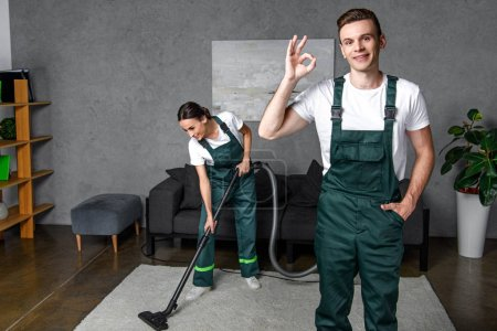 Photo for Smiling young cleaning company workers using vacuum cleaner and showing ok sign - Royalty Free Image