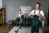 heureux jeune nettoyage des travailleurs de l'entreprise à l'aide de votre aspirateur et montrant les pouces vers le haut