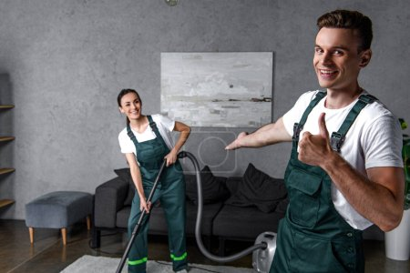 smiling young man showing thumb up and showing beautiful female cleaner using vacuum cleaner