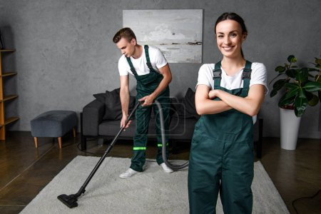 young male cleaner using vacuum cleaner and female coworker standing with crossed arms and smiling at camera