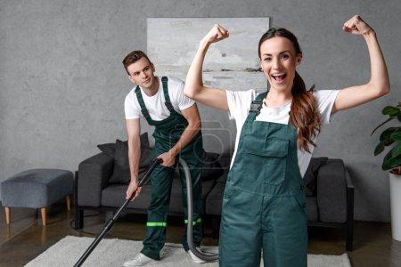 Photo pour Jeune nettoyeur masculin utilisant un aspirateur et regardant une collègue féminine montrant les muscles et souriant à la caméra - image libre de droit