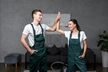 Photo for Happy young professional cleaning company workers smiling each other and giving high five - Royalty Free Image
