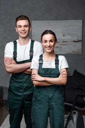 Foto de Limpiadores profesionales jóvenes alegres de pie con los brazos cruzados y sonriendo a cámara - Imagen libre de derechos