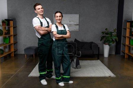 Photo pour Heureux jeunes nettoyeurs professionnels debout avec les bras croisés et sourire à la caméra - image libre de droit